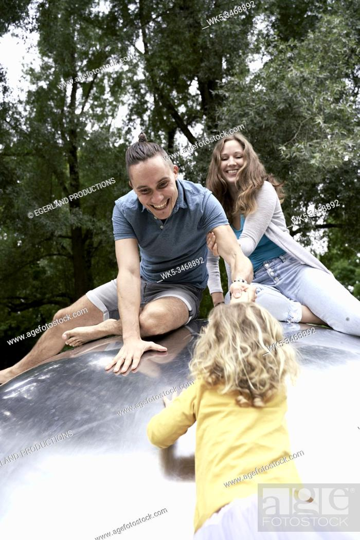 Stock Photo: Family in park playing on metal sphere. Munich, Germany.