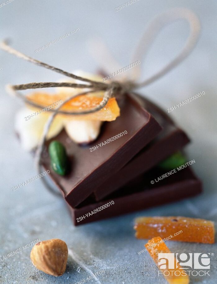 Stock Photo: Chocolate bars tied together with string, candied fruit, hazelnut.