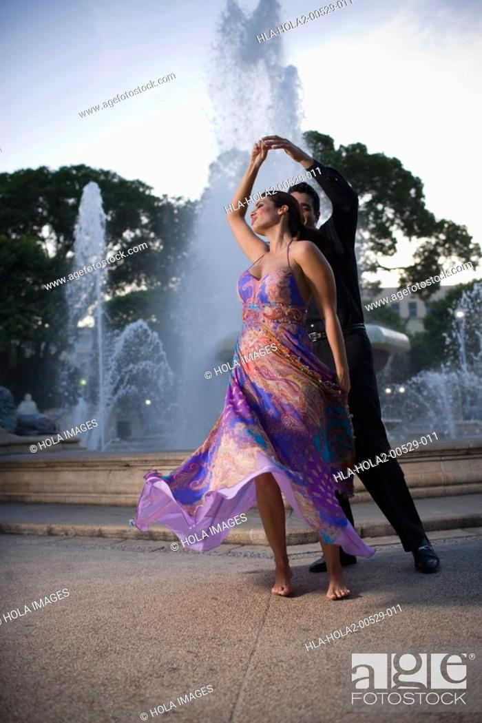 Imagen: Couple dancing by fountain in plaza.