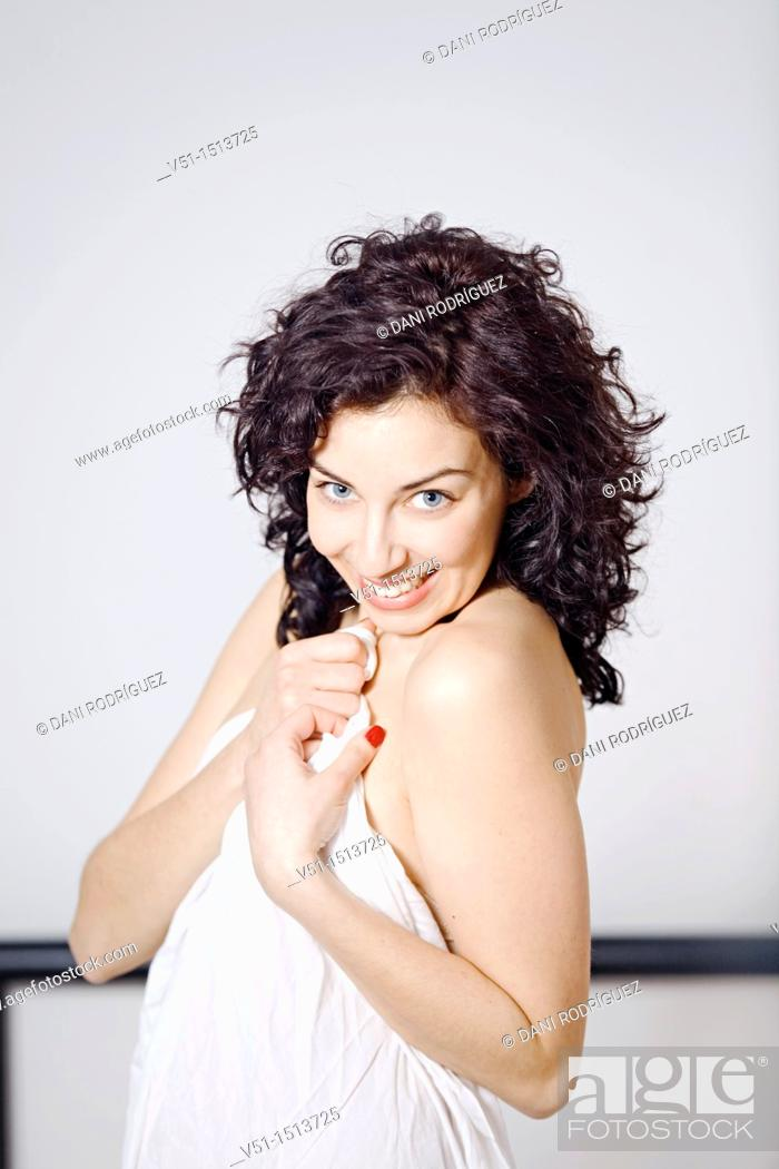 Stock Photo: Portrait of a beaitiful woman covering her body with sheets and smiling at camera.