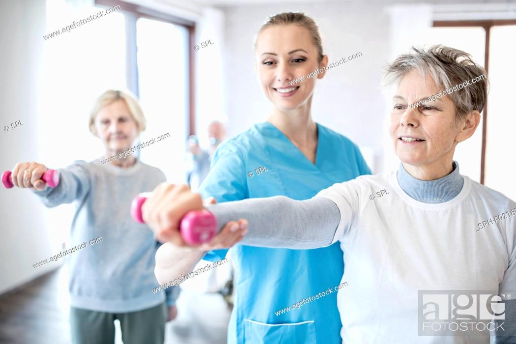 Stock Photo: Woman holding hand weight with physiotherapist.
