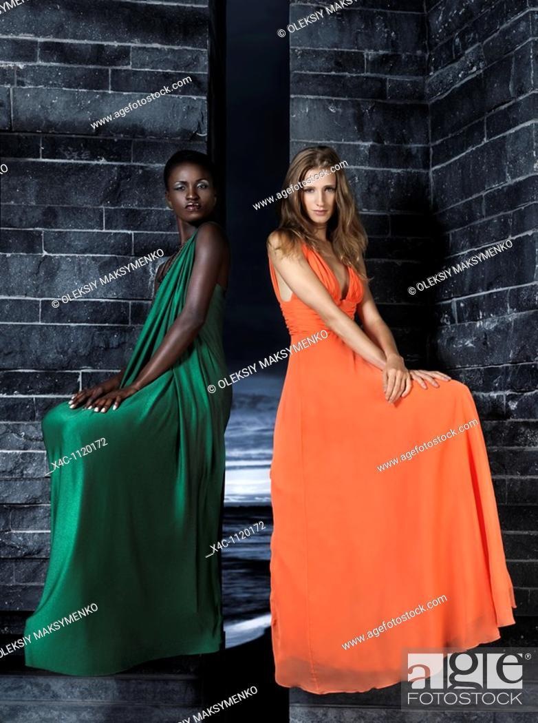 Stock Photo: Two beautiful women in elegant dresses sitting on a black stone wall  High fashion.