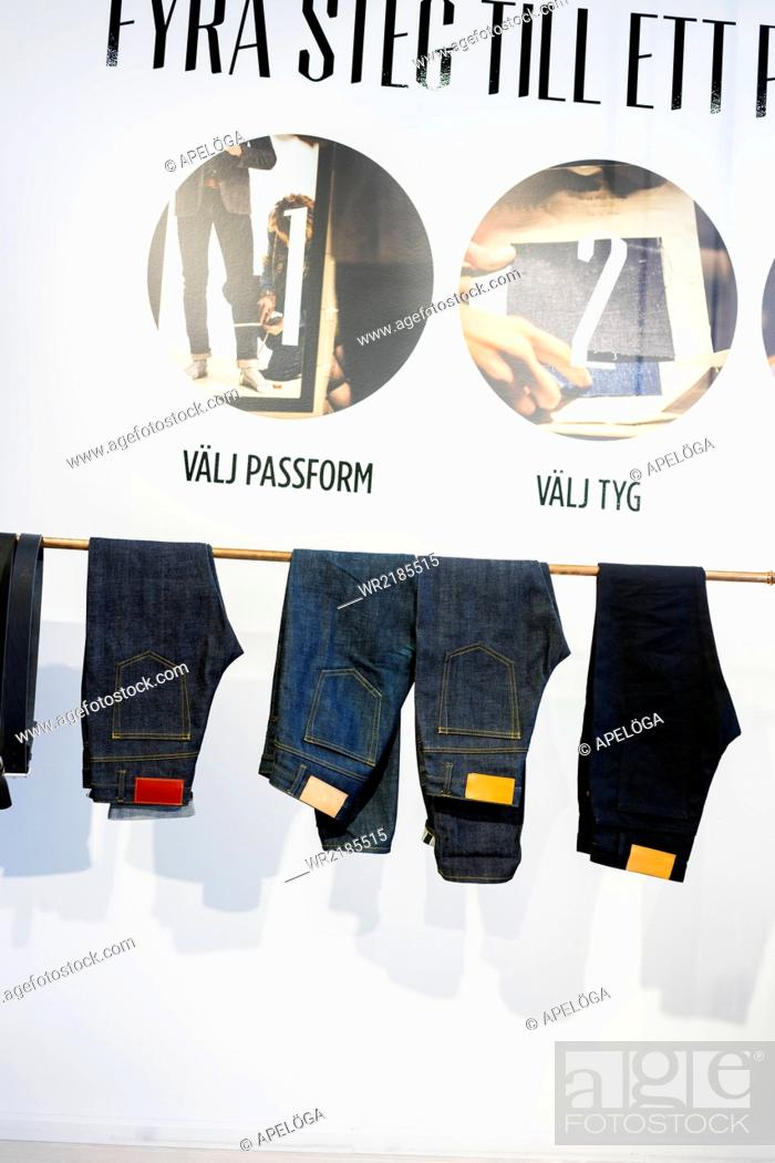 Stock Photo: Jeans hanging from rack in factory.