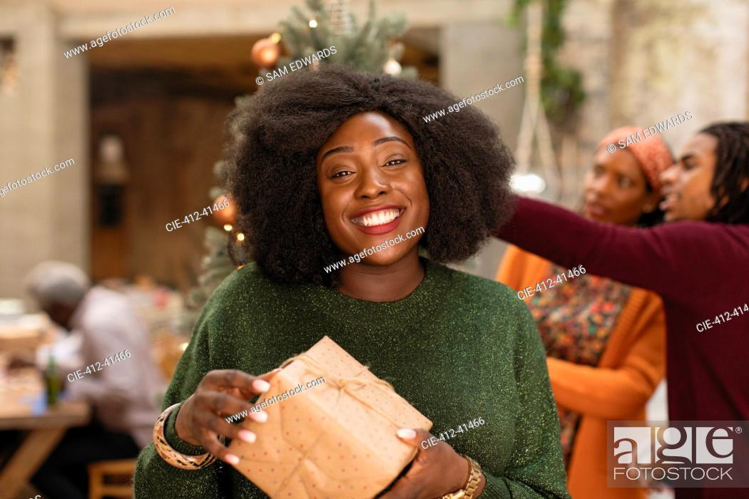 Stock Photo: Portrait smiling, confident young woman holding Christmas gift.