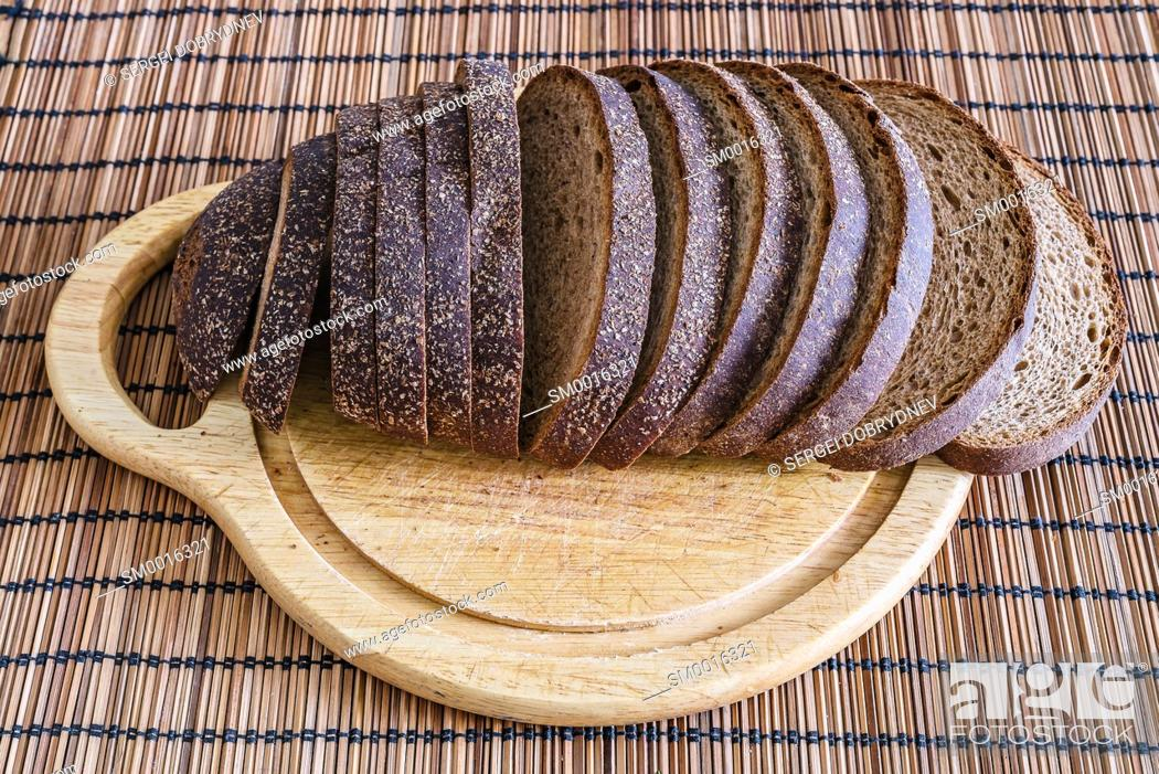Stock Photo: Sliced loaf of rye bread on a cutting board close up.