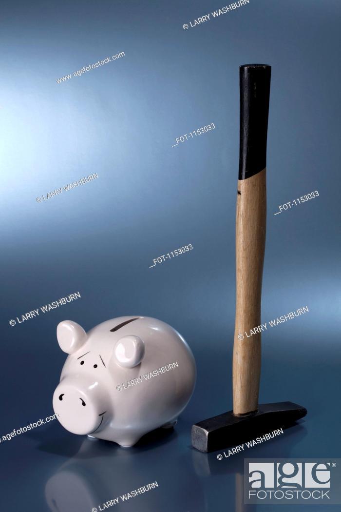 Stock Photo: A sledgehammer next to a ceramic piggy bank.