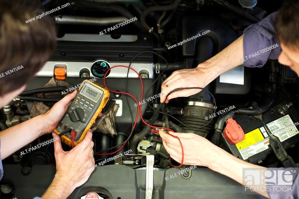 Stock Photo: Mechanics tuning car engine.