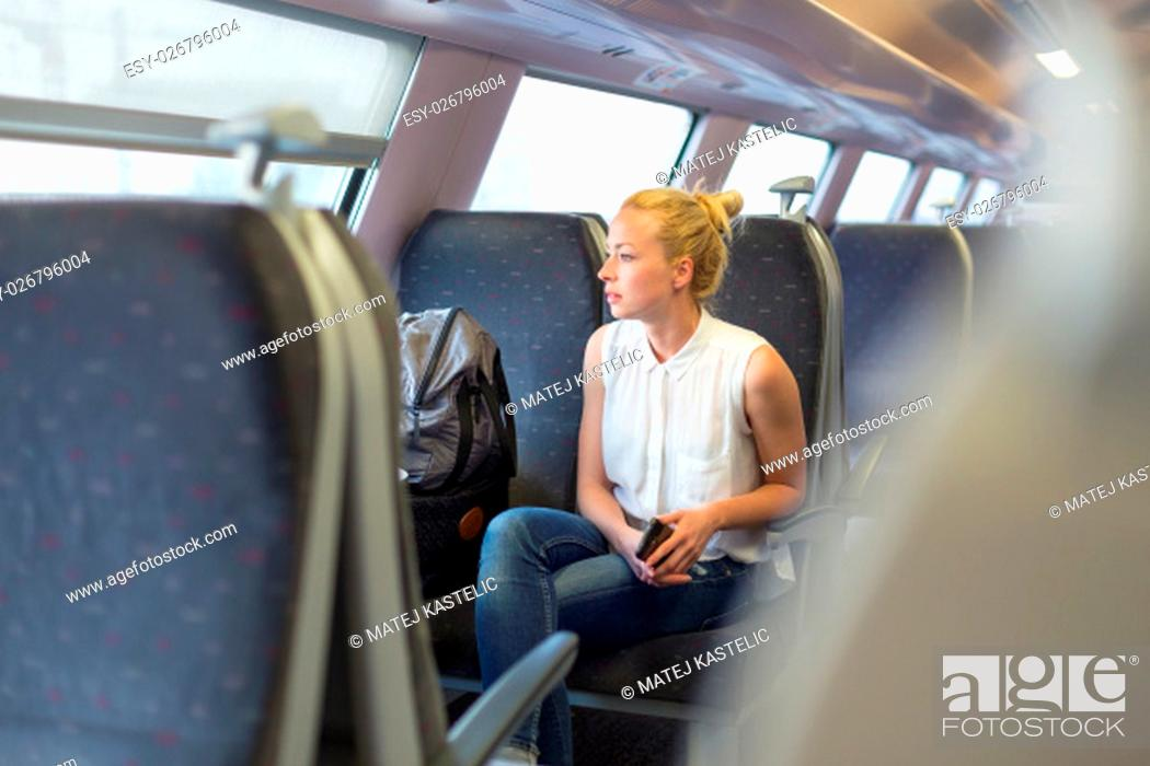 Stock Photo: Young woman looking trough window while traveling by train.