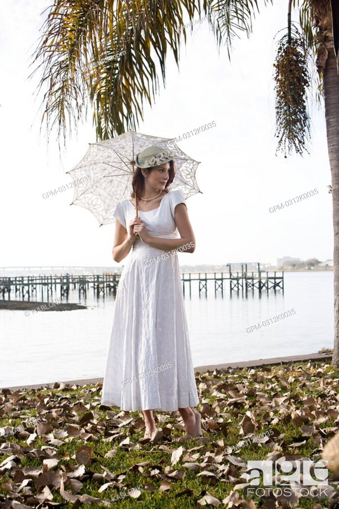 Imagen: Portrait of elegant lady in white dress holding umbrella on water's edge at a garden party.