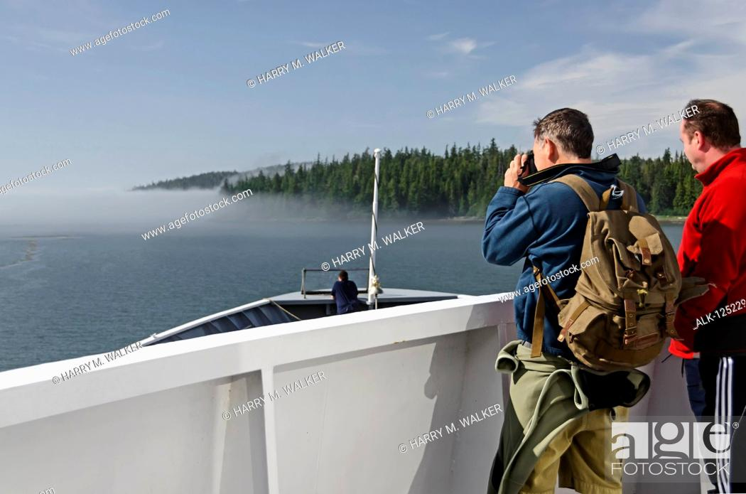Stock Photo: Two tourists watch as Alaska State Ferry approaches fog bank near the entrance of Sumner Strait from Wrangell Narrows, Southeast Alaska; Alaska.