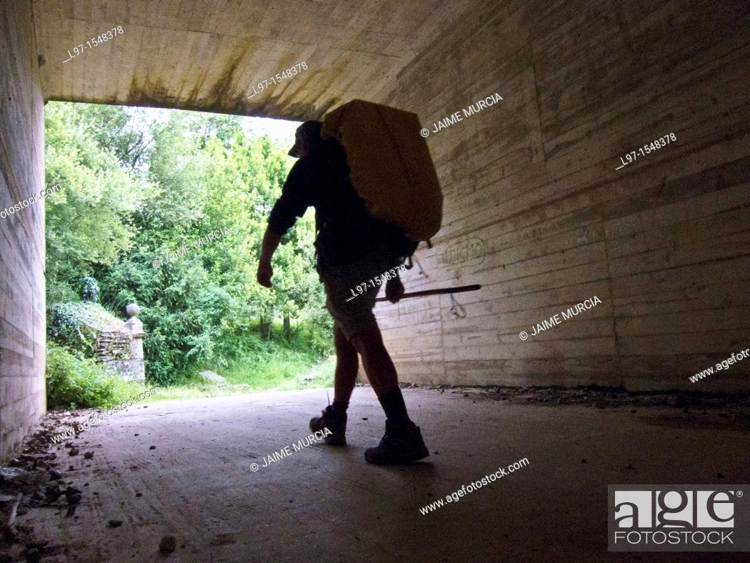 Stock Photo: Silhouette of a hiker walking through highway underpass along the Camino de Santiago.