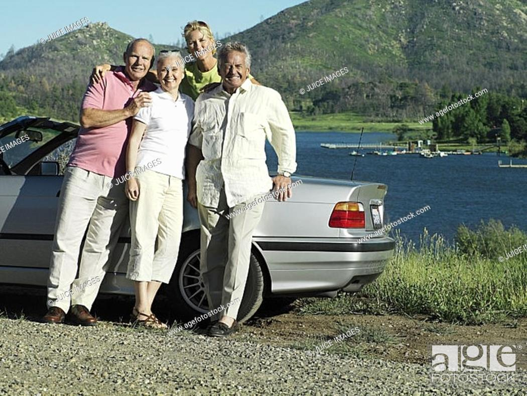 Stock Photo: Two senior couples standing beside convertible car near lake, smiling, portrait.