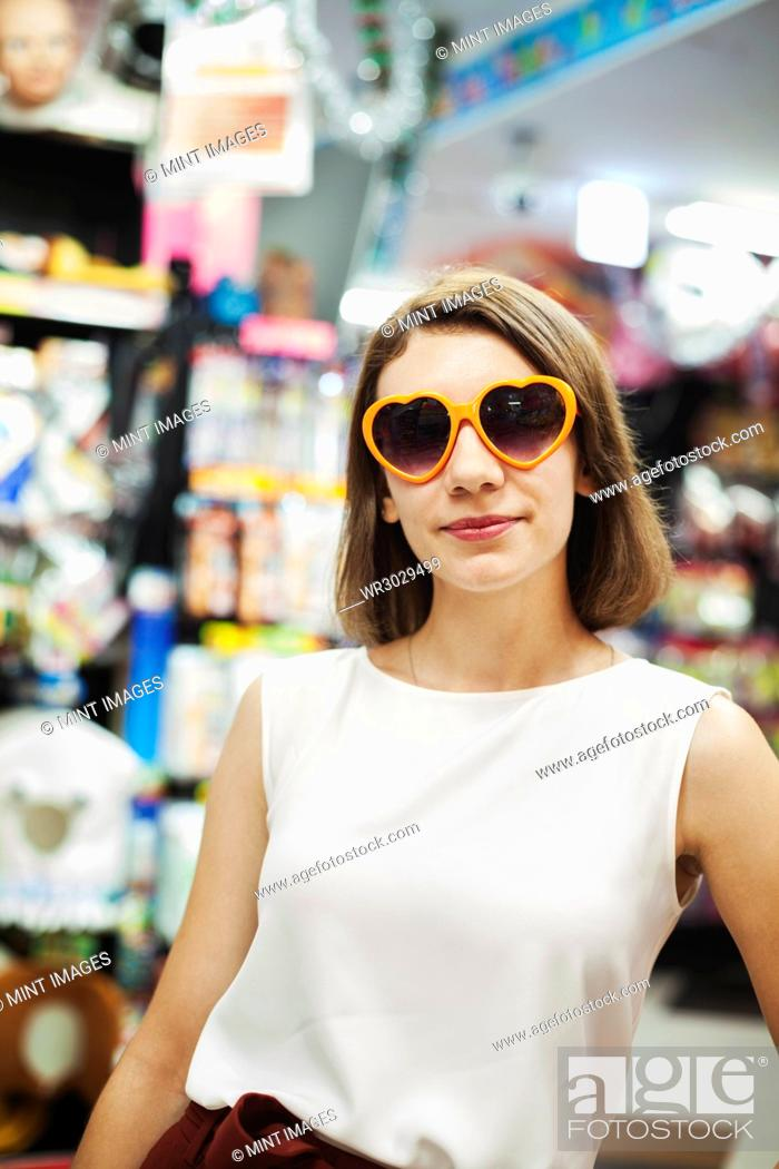 Photo de stock: Young woman with brown hair wearing white sleeveless top wearing orange heart shaped sunglasses, looking at camera.