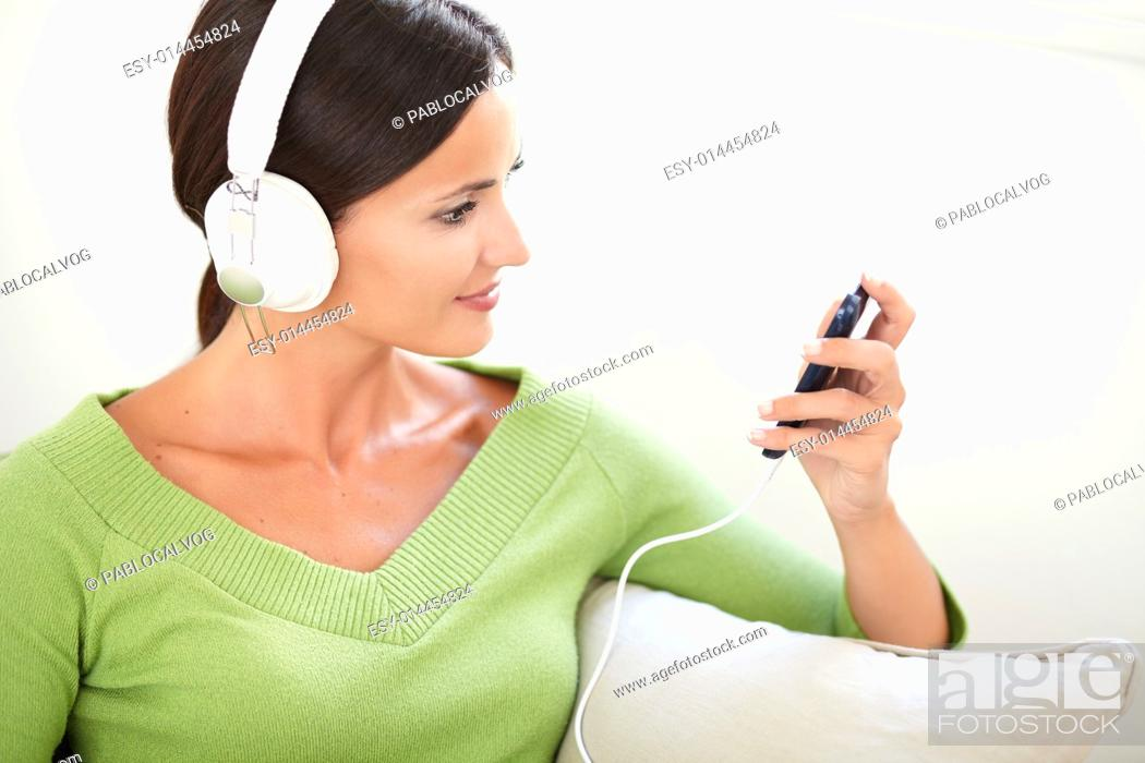 Stock Photo: Horizontal portrait of an attractive woman using a portable music player while sitting indoors.
