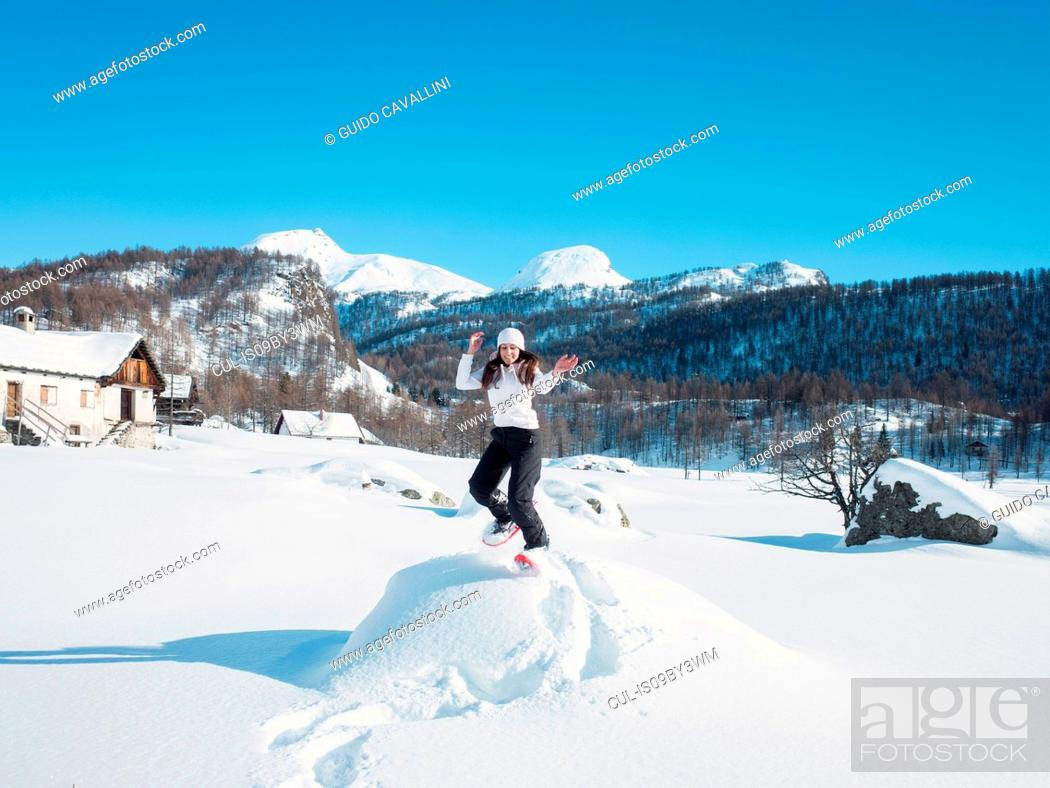 Photo de stock: Young woman in knit hat jumping in snow covered landscape, portrait, Alpe Ciamporino, Piemonte, Italy.