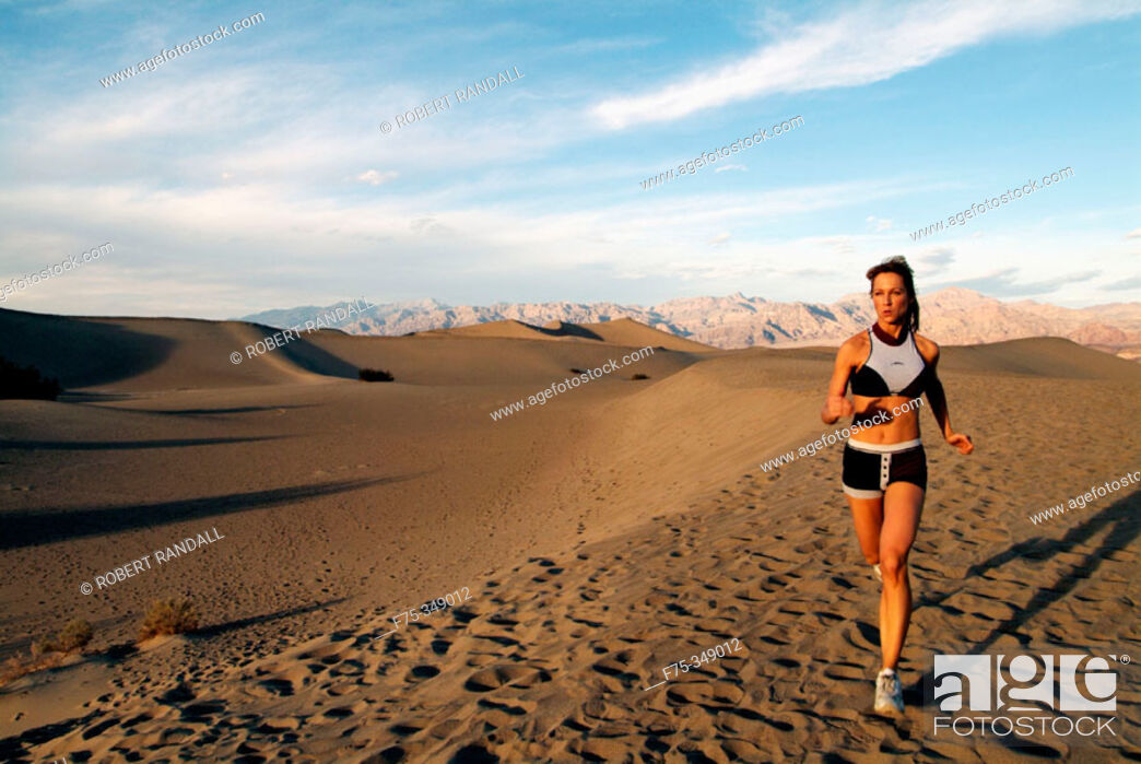 Stock Photo: Young woman running sand dunes in Death Valley, California. USA.