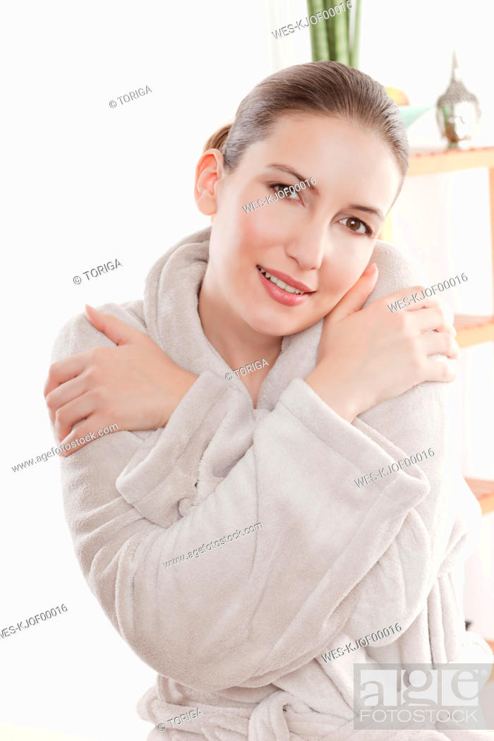 Stock Photo: Woman in bathrobe with arms crossed, smiling, portrait.