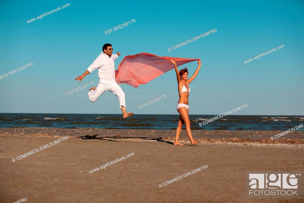 Stock Photo: happy, young couple walking along the seashore.