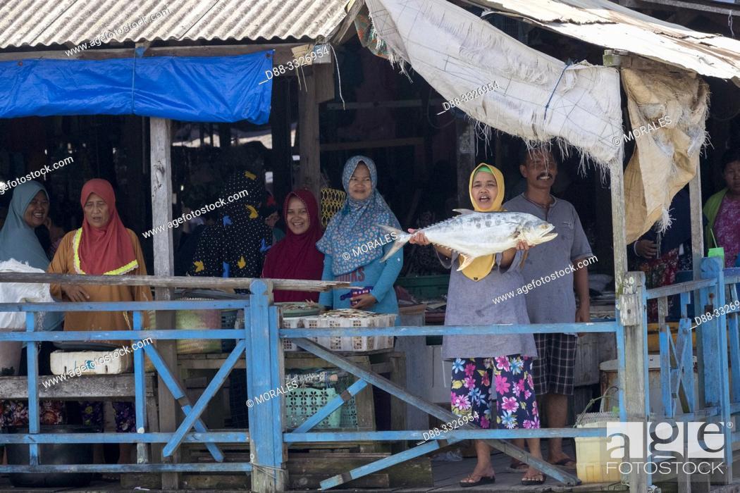 Stock Photo: Asie, Indonésie, Bornéo,Kalimantan, Ville de Kumai, marché aux poissons, femme montrant n poisson/ Asia, Indonesia, Borneo, Tanjung Puting National Park.