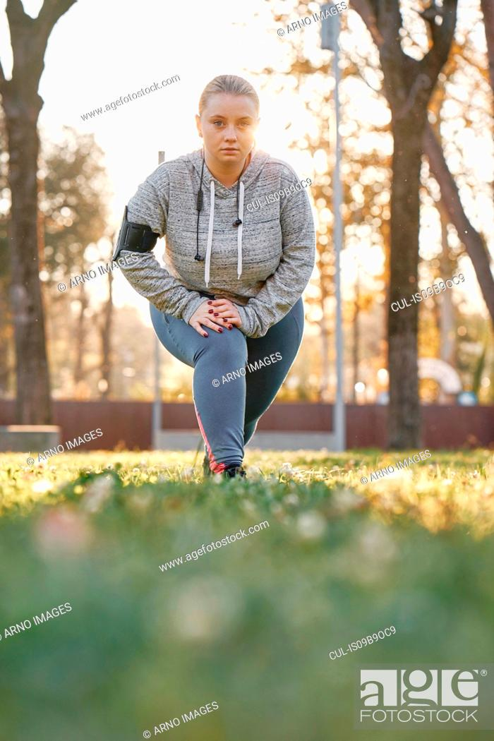 Photo de stock: Portrait of curvaceous young woman training in park, leaning forward and crouching.