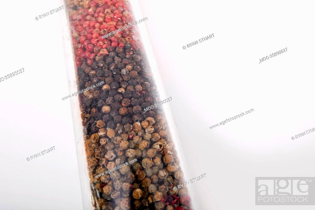 Stock Photo: Various peppercorns in package against white background.