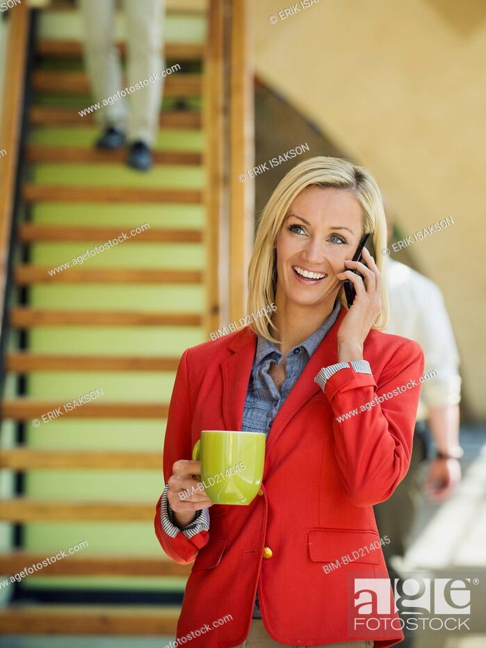 Imagen: Businesswoman talking on cell phone near staircase.
