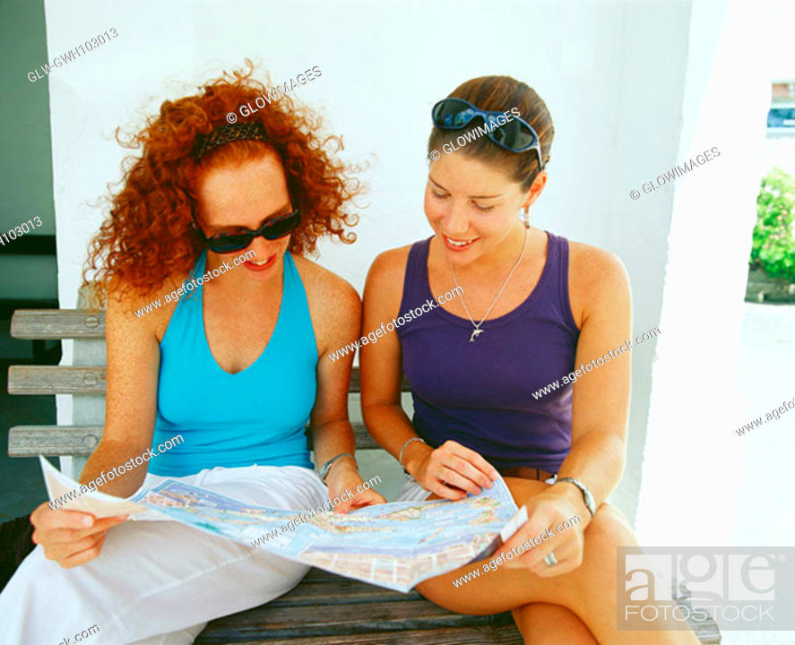 Stock Photo: Close-up of two young women sitting on a bench and reading a newspaper, Bermuda.