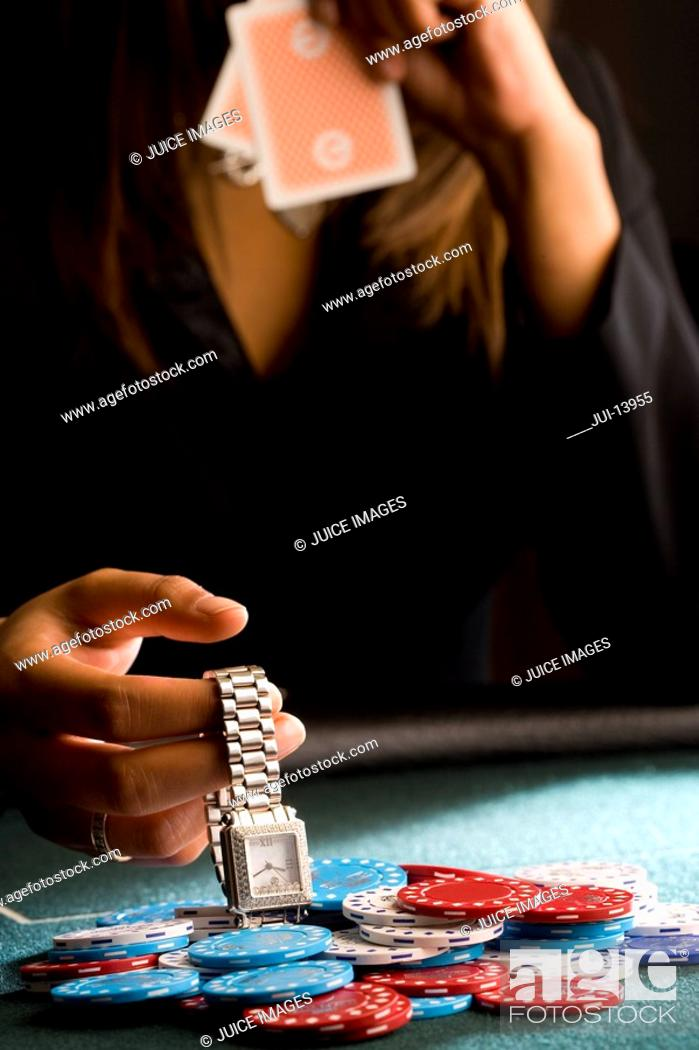 Stock Photo: Woman placing watch on pile of gambling chips on table, mid section.