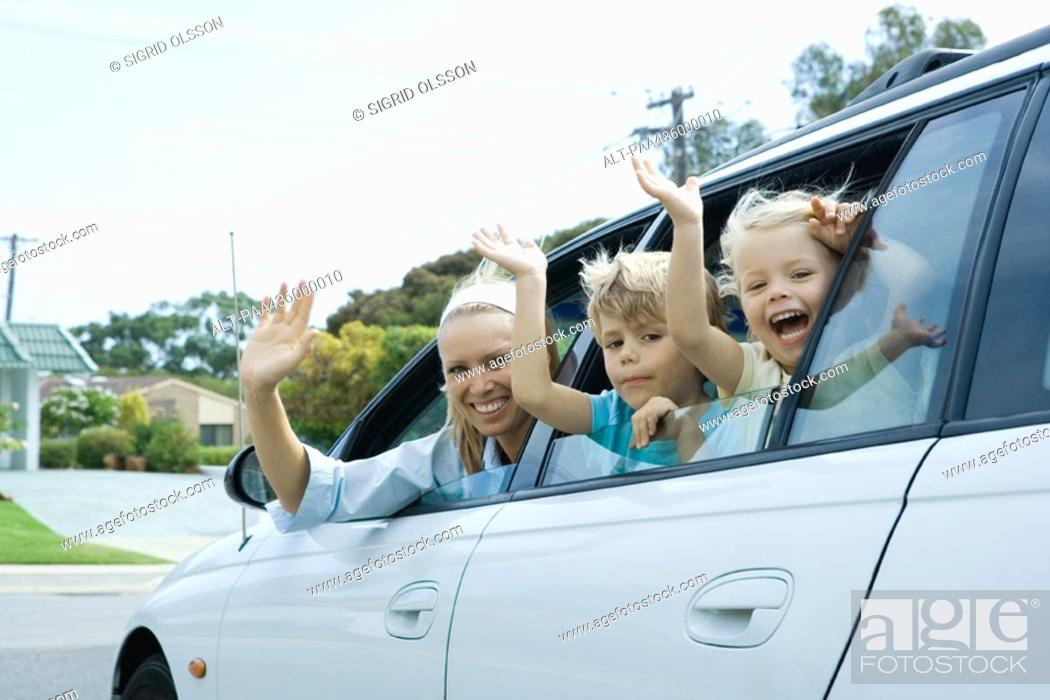 Stock Photo: Mother and two children waving out of car windows, looking at camera.