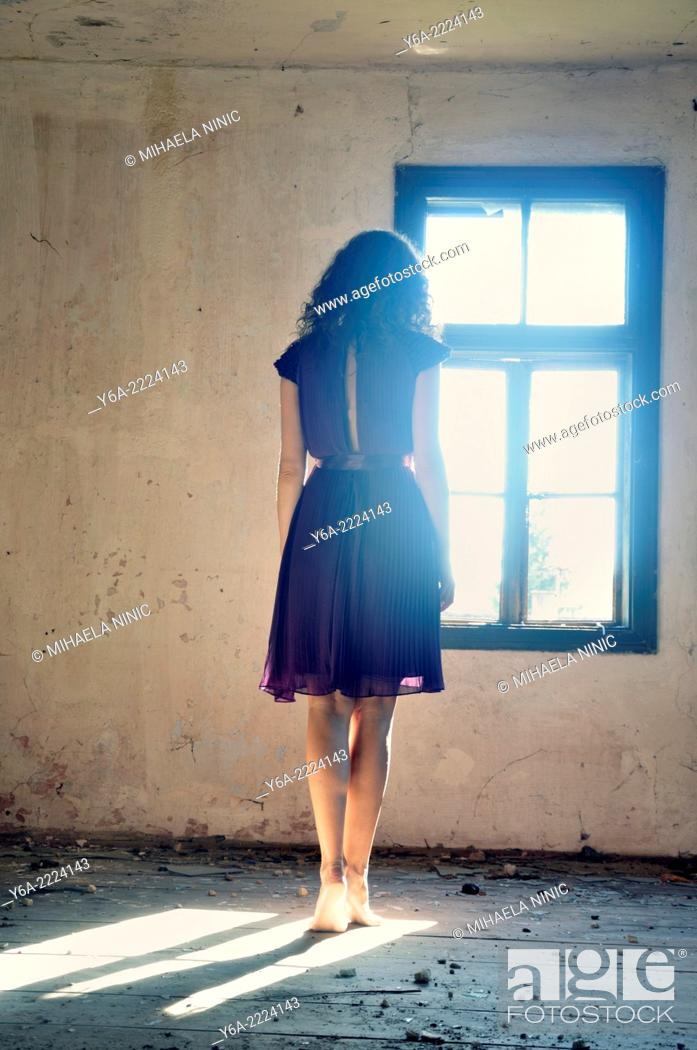 Stock Photo: Young woman standing by the window.