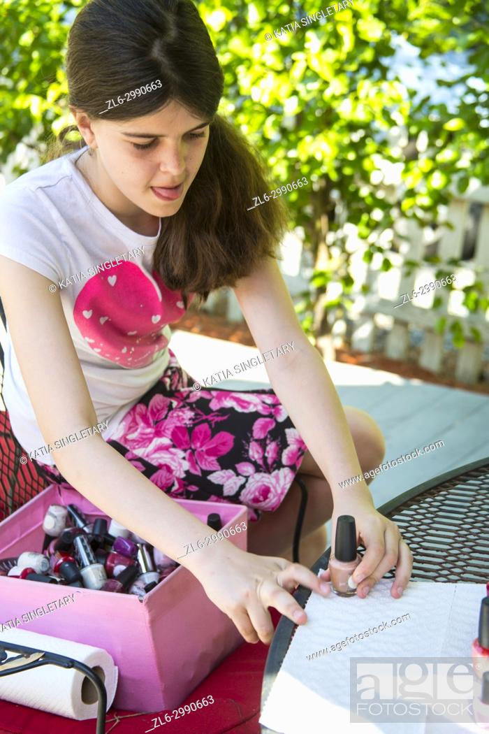 Stock Photo: Caucasian pre teen girl 11 years old, with long hair making an art, craft project for Easter with nail polish and water to color eggs.