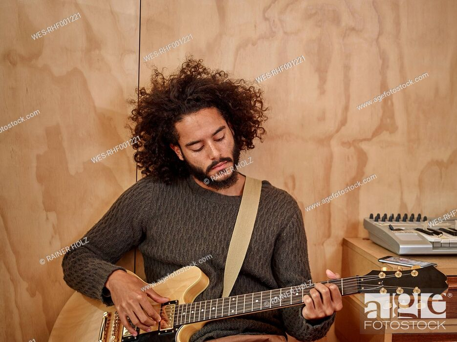 Stock Photo: Young man playing electric guitar.