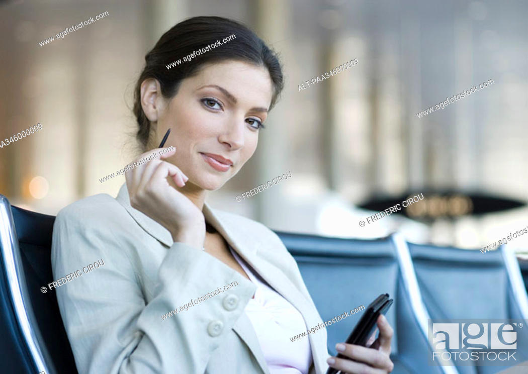 Stock Photo: Businesswoman using electronic organizer in airport lounge, smiling at camera.