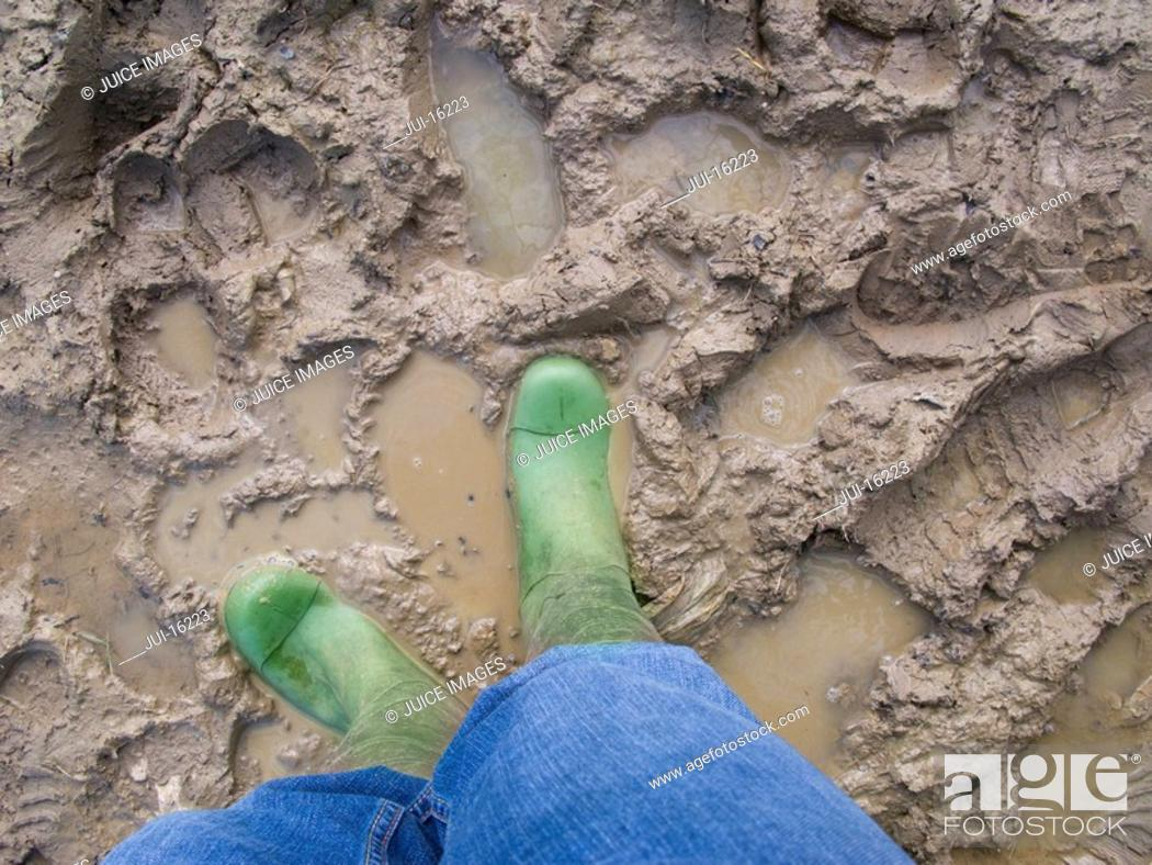 Stock Photo: Person in rubber boots standing in mud.