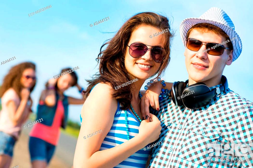 Stock Photo: young couple standing on the road, having fun with friends.
