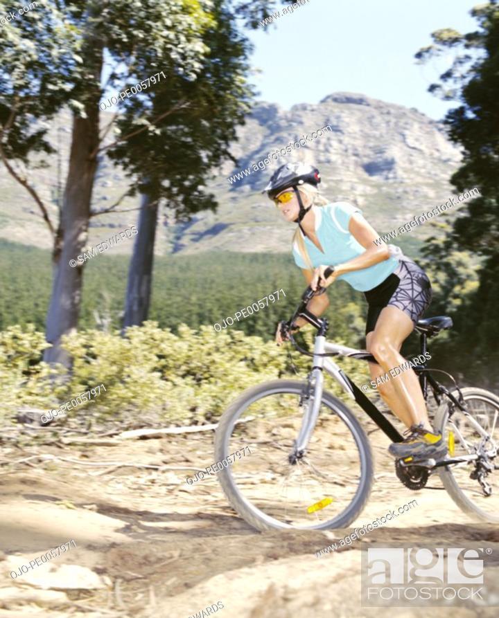 Stock Photo: A woman mountain biking.