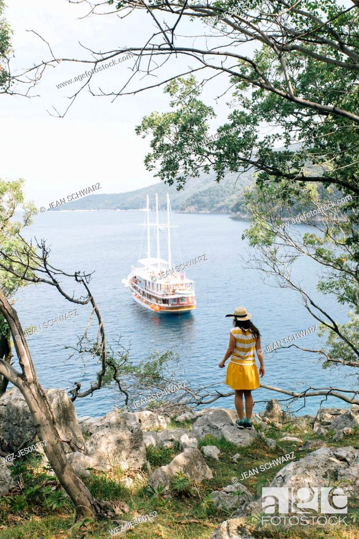Stock Photo: Croatia, Cres, woman standing at the coast looking at the sea with sailing ship.