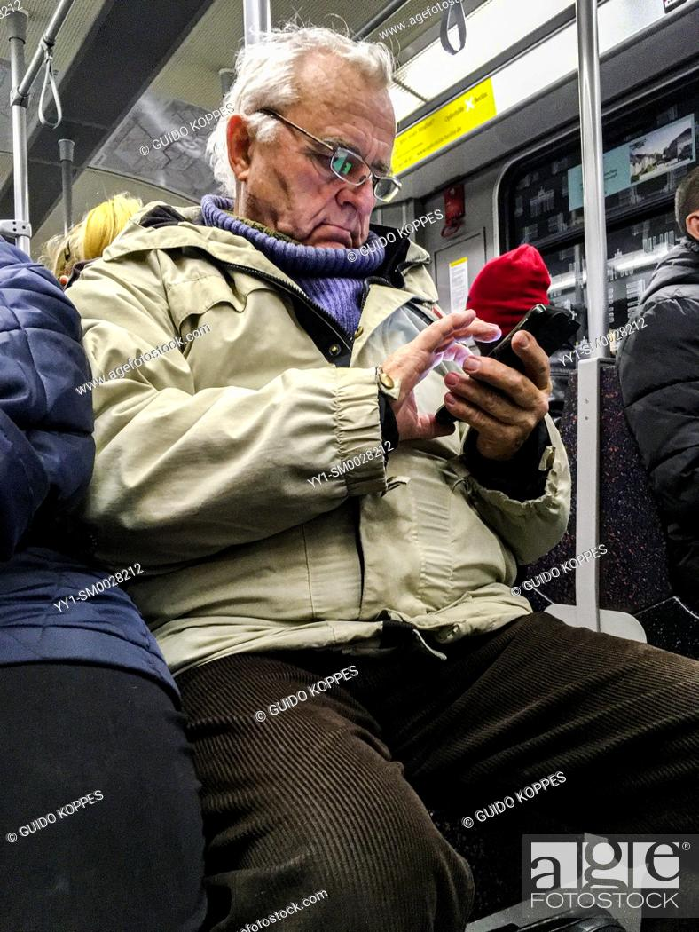Stock Photo: Berlin, Germany. Elder man concentrated on his smartphone, while taking a subway ride underneath the city of Berlin.