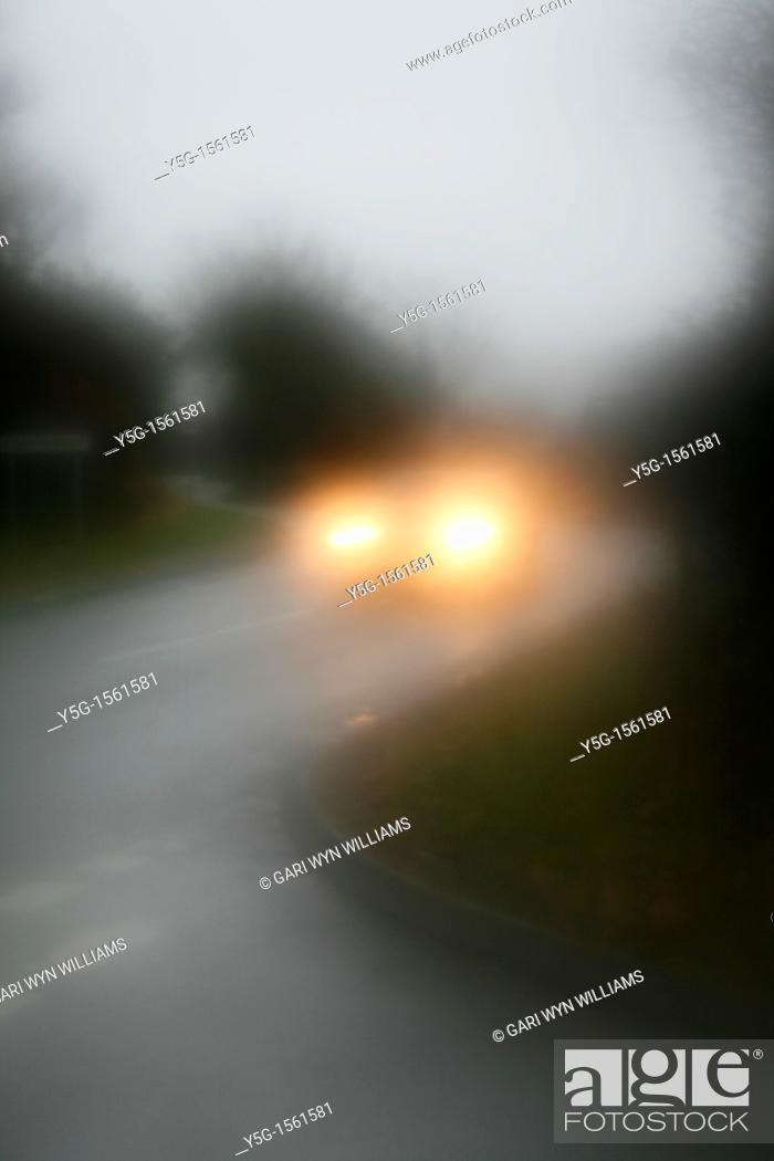 Stock Photo: car driving in heavy rain on rural country road.