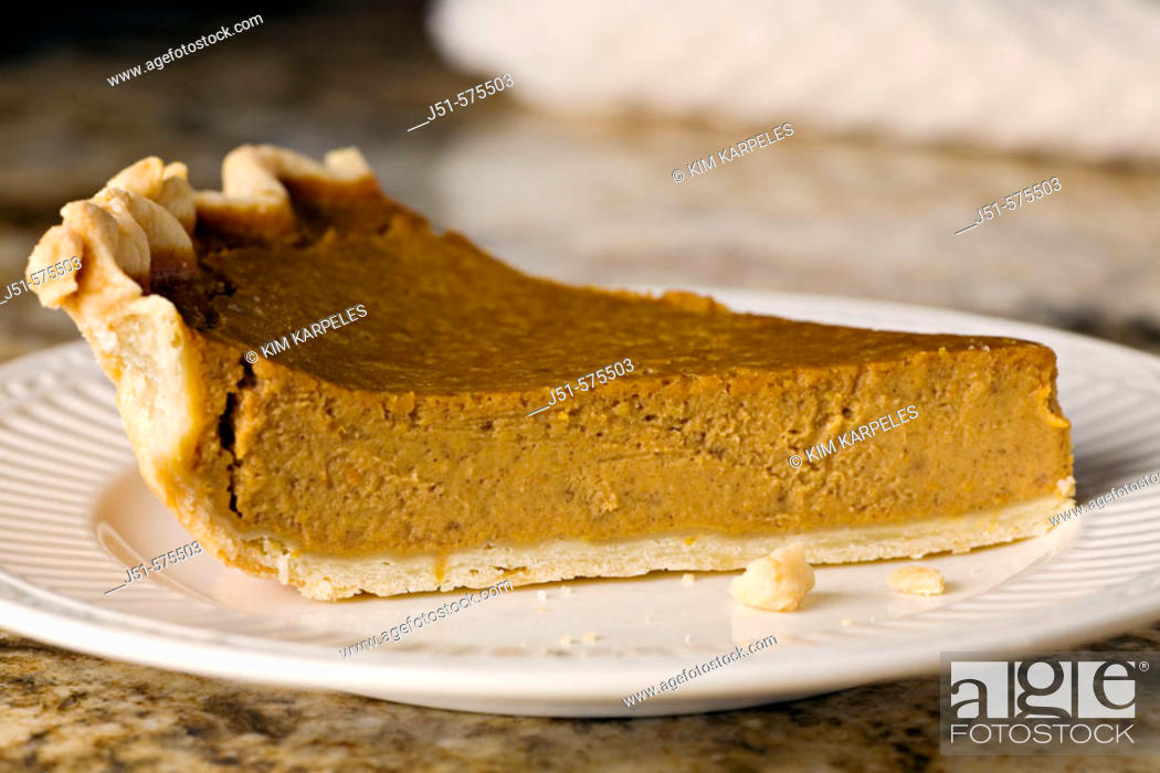 Stock Photo: Food. Riverwoods, Illinois. One slice of homemade pumpkin pie and crumbs on white plate white napkin on granite counter top.