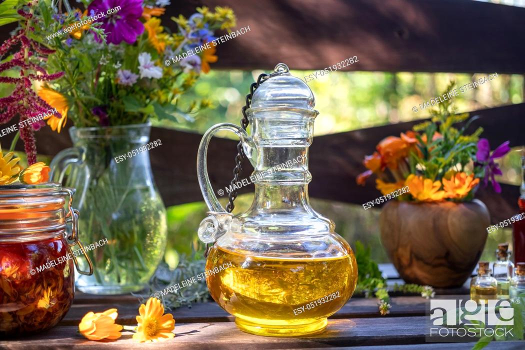 Stock Photo: Bottles of herbal and essential oils, with fresh medicinal plants and flowers in the background.