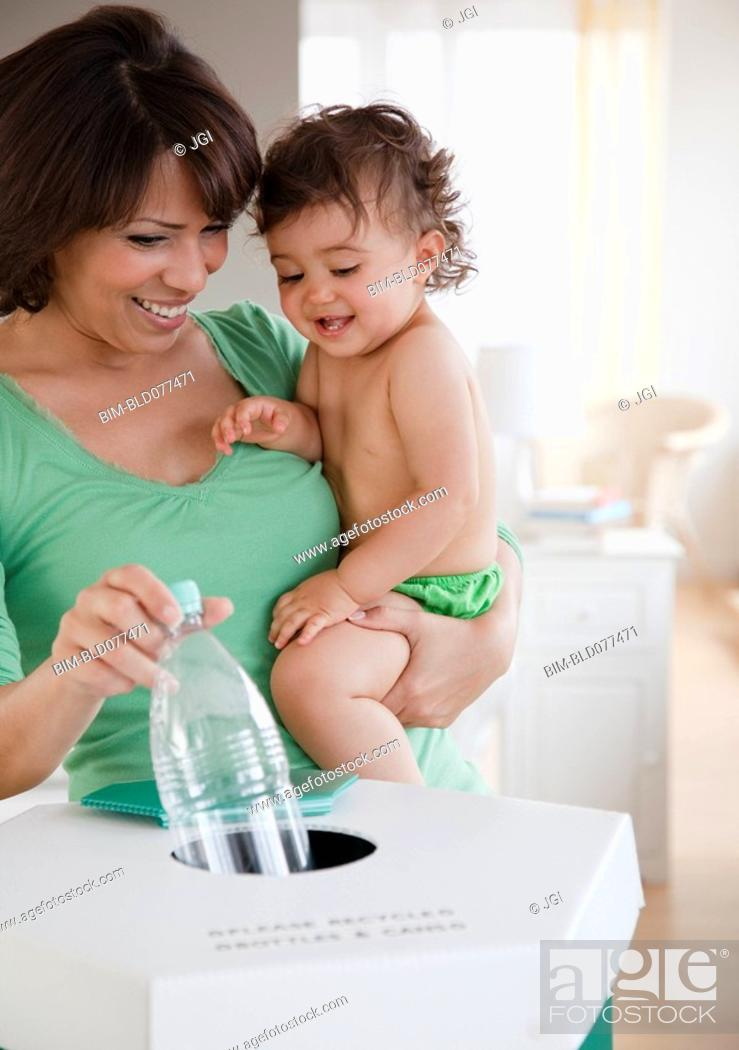 Stock Photo: Hispanic mother teaching daughter about recycling.