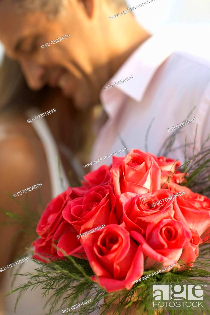 Stock Photo: Newlyweds hugging focus on flowers.