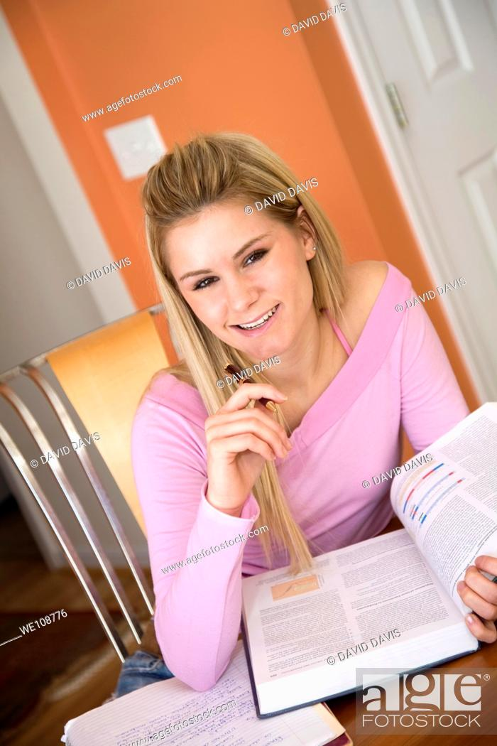 Stock Photo: Caucasian college student working on home work.