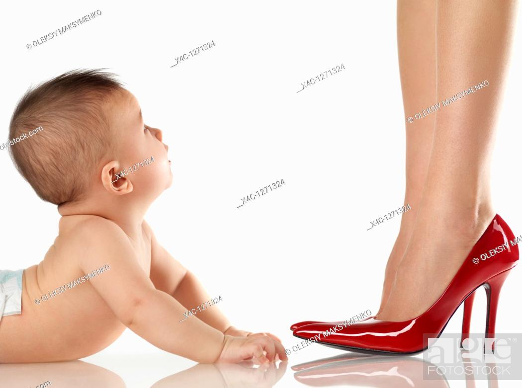 Stock Photo: Six month old baby boy looking up at his dressed up mother wearing red high heel shoes.