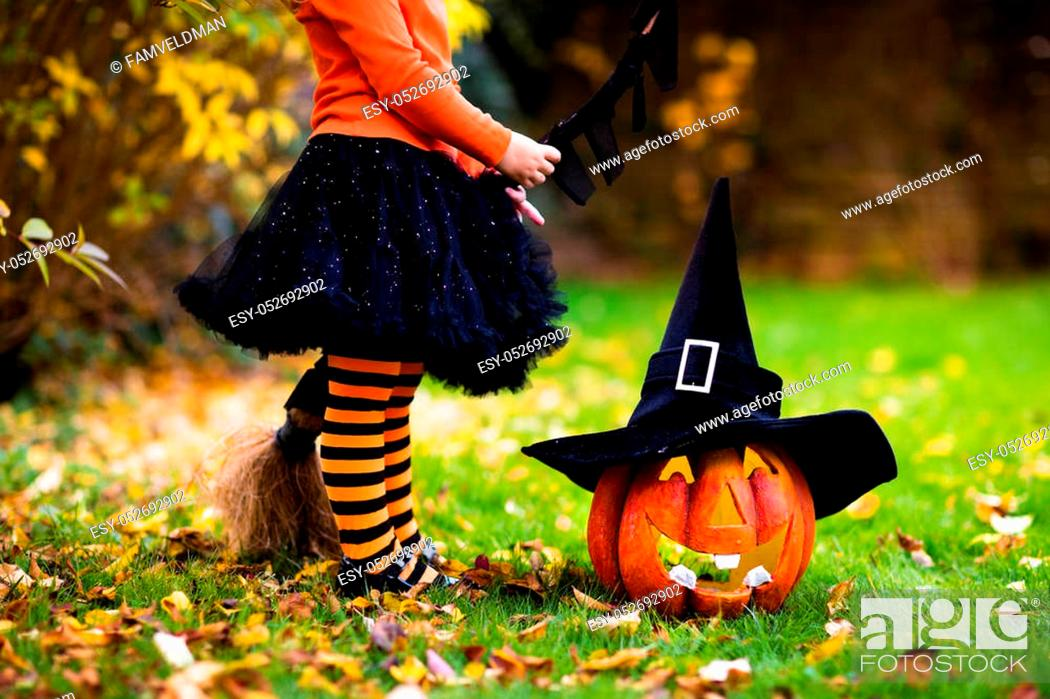 Stock Photo: Little girl in witch costume playing in autumn park. Child having fun at Halloween trick or treat. Kids trick or treating.