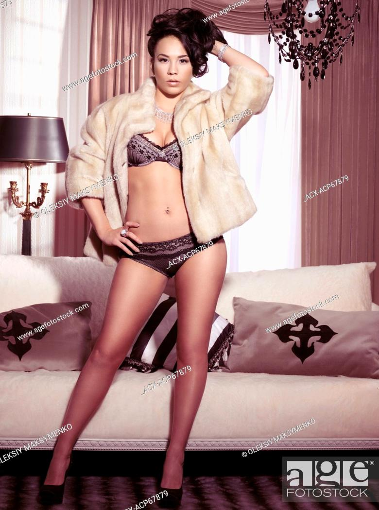 6e15d0e39e7 Stock Photo - Glamour photo of a young woman wearing lingerie and fur coat  standing in front of a window in a room