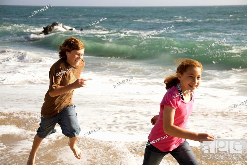 Stock Photo: A caucasian boy playfully chases a young mixed race Mexican & caucasian girl on a beach in Santa Cruz, California.