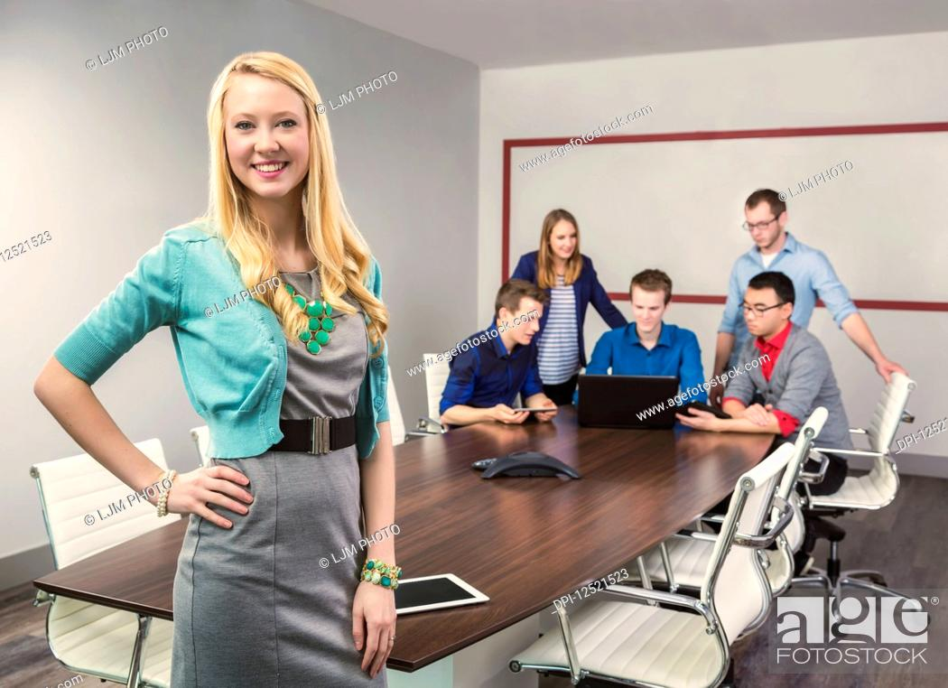 Stock Photo: A beautiful young millennial business woman working on her tablet in a conference room with her co-workers; Sherwood Park, Alberta, Canada.