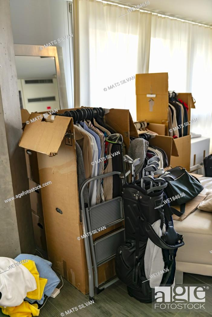 Stock Photo: Moving House with Cardboard Boxes and Clothes and Golf Bag in Living Room in Switzerland.